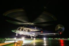 在近海油和煤气平台的直升机着陆在甲板或停车场 直升机飞行员夜间飞行训练  免版税图库摄影