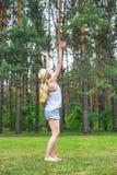 在近绿草草坪的快乐的年轻白肤金发的式样跳舞 免版税库存照片