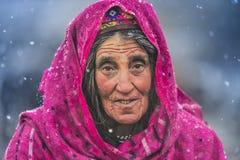 在返回的雪等待的动物中间的老妇人从牧场地 库存图片