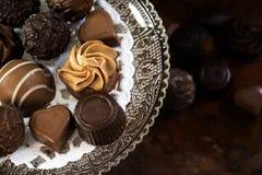 在进一步被弄脏玻璃的étagère的巧克力果仁糖和 库存图片