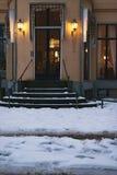 在进口旁边的有启发性灯笼与多雪的楼梯 免版税库存照片