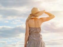 在远处看反对多云蓝天背景的帽子和礼服的美丽的女孩 免版税图库摄影