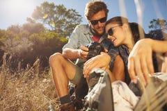 在远足休假的旅行的夫妇坐和看pict 图库摄影