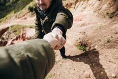 在远足在一个山区期间,远足者给一只手另一个人 库存照片