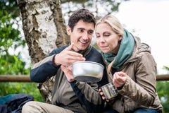 在远足期间的背包徒步旅行者吃在罐子碗外面的 图库摄影