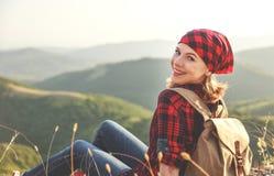 在远足期间,在山顶部的妇女游人在户外日落 库存照片