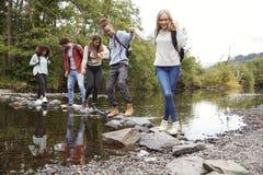 在远足期间,握手走在岩石的多族群五个年轻成人朋友横渡小河 免版税库存照片