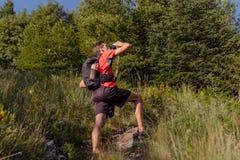 在远足期间,有背包的人采取休息和喝从水瓶 免版税图库摄影