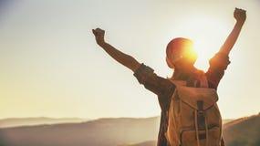 在远足期间,在山顶部的妇女游人在户外日落 图库摄影
