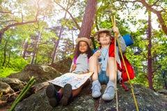 在远足男孩和女孩期间有地图的,孩子休息 免版税图库摄影