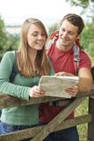在远足的夫妇通过看地图的乡下 库存照片