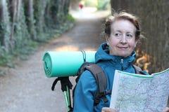 在远足的妇女常设读书地图在乡下 免版税图库摄影