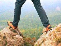 在远足长裤和皮革迁徙的鞋子在岩石峰顶的黑暗的男性腿在有薄雾的谷上 小山概述  免版税库存照片