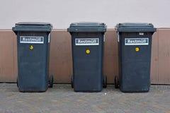 在连续站立在房子墙壁上的轮子的3个小黑残余的废物箱在城市 免版税库存图片