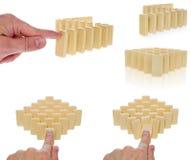 在连续被安排的一种乳脂状的颜色的多米诺由手指b按了 免版税库存照片