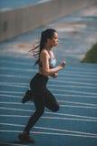 在连续轨道体育场的女运动员训练,女孩连续概念 免版税图库摄影