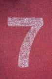 在连续轨道的第七 在红色橡胶跑马场的白色轨道数字 库存图片