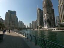 在迪拜小游艇船坞的走的散步有地平线、大厦和游艇看法  库存图片