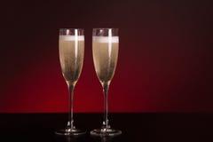 在迷人的红色背景的两块典雅的香槟玻璃 库存照片