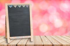 在迷离花桃红色背景的木台式与空白的黑板的 免版税库存图片