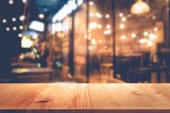 在迷离bokeh咖啡馆或餐馆背景的木桌 库存照片