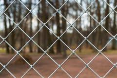 在迷离公园背景的钢刺耳栅格 库存图片