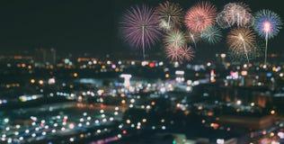 在迷离城市地平线背景的五颜六色的烟花在晚上 图库摄影