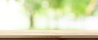 在迷离树绿色背景的木台式在公园 免版税库存照片