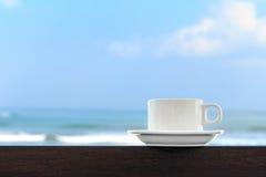 在迷离海滩和蓝天背景的加奶咖啡杯子 免版税库存图片