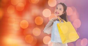 在迷离背景的微笑的妇女运载的购物袋 库存图片
