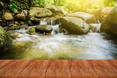 在迷离自然瀑布的木台式与阳光 库存图片