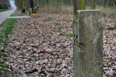 在适宜游览的路旁边的石里程碑 库存图片