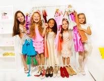 在选择衣裳的购物期间的愉快的女孩 免版税库存图片