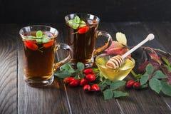 在透明杯子的玫瑰果茶用蜂蜜和新鲜的莓果 维生素C饮料 库存照片