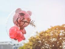 在透明气球的红色玩具熊有毕业生的祝贺文本的 免版税库存图片