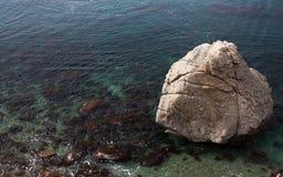 在透明海水的大石头 免版税库存图片