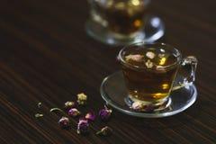 在透明玻璃杯子的罗斯东方茶在黑暗的木背景 免版税图库摄影