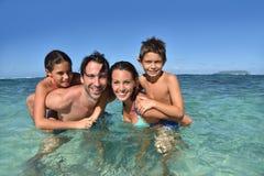 在透明的海水的快乐的家庭游泳 库存图片