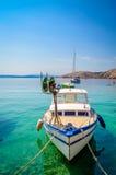在透明的蓝色海的一个船坞栓的小船 库存照片