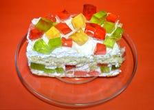 在透明盘的开胃果冻蛋糕在红色背景 免版税库存照片