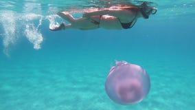 在透明蓝色的慢动作水下的游泳摄制的一年轻美女与Rhizostoma pulmo,一般叫作ba 股票视频