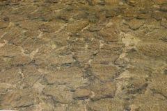 在透明运河下的石头 免版税库存照片