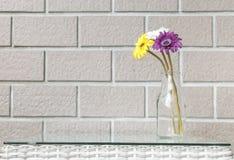 在透明玻璃瓶的特写镜头人为五颜六色的花在被弄脏的棕色砖墙纹理背景的木织法桌上 免版税库存图片