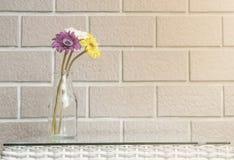 在透明玻璃瓶的特写镜头人为五颜六色的花在被弄脏的棕色砖墙纹理背景的木织法桌上 库存照片