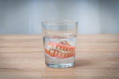 在透明水玻璃的假牙游泳 免版税图库摄影