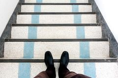 在逐步减低的楼梯的黑鞋子 库存照片