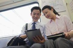 在途中的地铁的愉快的企业夫妇工作 免版税图库摄影