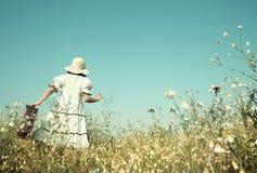 在途中的女孩对她的未来走在有h的一个用花装饰的草甸的 免版税库存图片