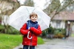 在途中的小白肤金发的孩子男孩对学校走在雨夹雪、雨和雪期间的与一把伞在冷的天 免版税库存图片