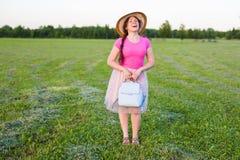 在逗人喜爱滑稽笑的画象或有背包和帽子的惊奇的妇女 免版税库存图片